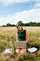 Young woman using a laptop computer in the middle of a field