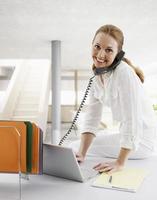 Empresaria de mediana edad con teléfono y computadora portátil
