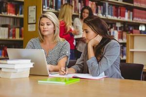 estudiantes enfocados en la computadora portátil con compañeros de clase detrás de ellos foto