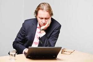 Hombre de negocios joven con el pelo rubio que trabaja con la computadora portátil. foto