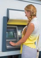 Linda mujer retirando dinero de un cajero automático.