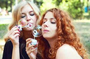 Two girlfriends blowing soap bubbles
