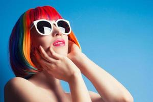 bella mujer con peluca colorida y gafas de sol blancas contra foto