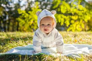 Cute caucasian baby boy in park looks at camera photo