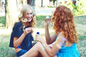 Two girlfriends blowing soap bubbles photo