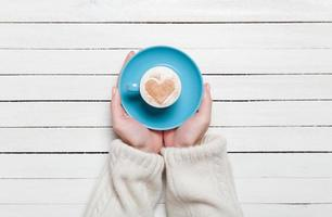 Female hands holding cup of coffee on wooden table. photo