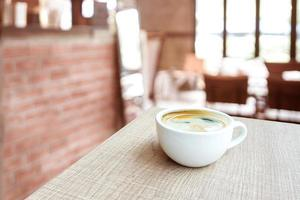 Coffee cup on wood table in cafe with blur cafe