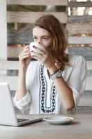 mujer joven con laptop mientras bebe té foto
