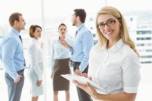 Businesswoman writing notes with colleagues behind