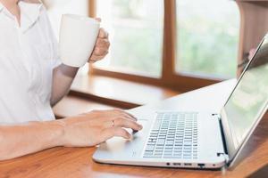 joven usa laptop, tomando café o té en el lugar de trabajo foto