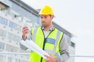 arquitecto utilizando teléfono inteligente contra la construcción