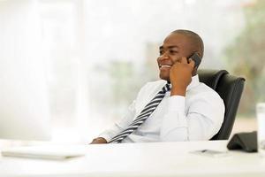 Ejecutivo de negocios africano hablando por teléfono fijo foto