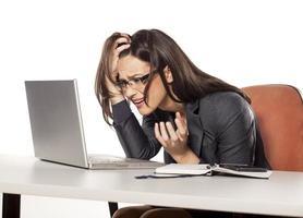 geschokte jonge onderneemster die in haar laptop kijkt