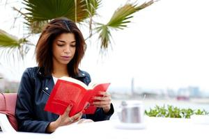 Young female hipster fascinating read book in open air