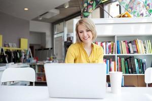 Gerente de mujer trabajando en la computadora portátil en la librería foto