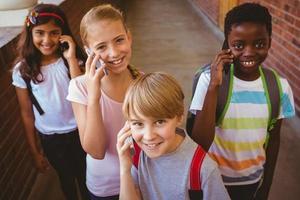School kids using cellphones in school corridor photo