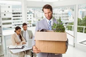 Businessman carrying his belongings in box photo