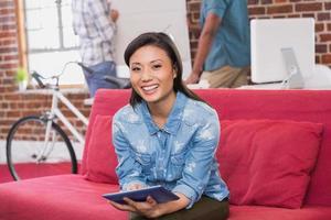 mujer casual con tableta digital en el sofá foto