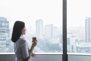 Businesswoman holding coffee cup and looking out the window