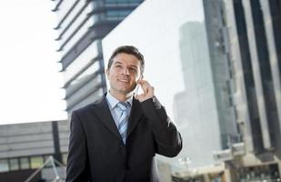 attractive businessman in suit talking on mobile phone happy outdoors