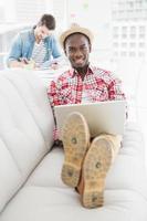 empresario alegre usando la computadora portátil en el sofá foto