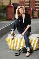 Sad beautiful woman sitting on the city sidewalk
