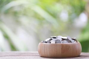 Moneda de plata en un tazón de madera. foto