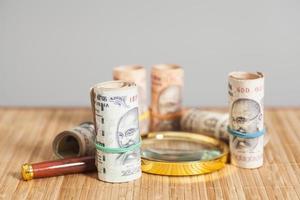 rolos de notas de rupia moeda indiana com lupa