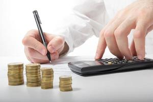 Business concept. Businessman's hand counting money on calculator