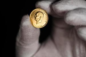 Kurush Ataturk Gold Coin Held with White Glove photo