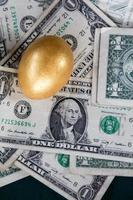 Single gold nest egg on US dollars