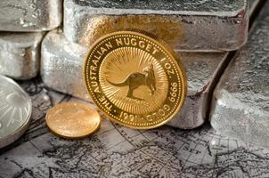 Australian Gold Coin Nugget infront of Silver Bars