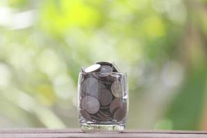 silver coin in glass is placed on a wood floor.