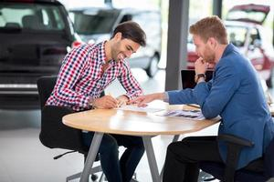 Happy man buy new vehicle in car showroom