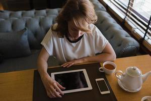 mujer joven con pantalla táctil durante el descanso para tomar café