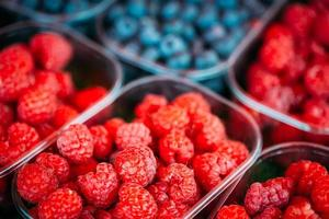 Baskets Full Of Raspberries And Blueberries On The Farmers Marke photo
