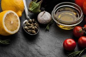 Olive oil with vegetables , lemon and capers