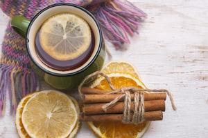 Сup of hot tea with lemon and scarf. Winter time. photo