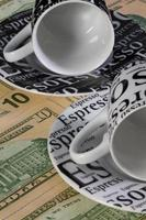 Two empty coffee cups  and US dollar banknotes