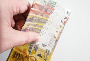 mano recogiendo una pila de billetes de franco suizo foto