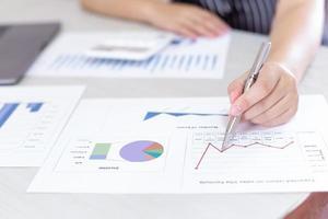 Der Geschäftsmann am Schreibtisch analysiert das Diagramm des Finanzwachstums
