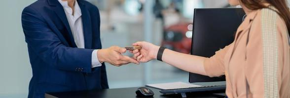 Closeup of an Asian receptionist handing over car keys at auto dealership photo