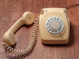 Teléfono retro en mesa de madera en frente fondo degradado foto