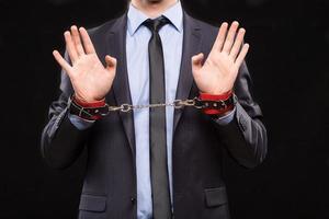 Hombre en un traje de negocios con las manos encadenadas. esposas para foto