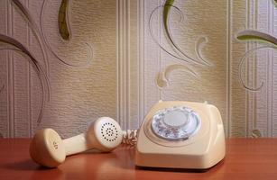 telefone retro na mesa de madeira em frente fundo gradiente