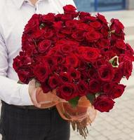 man in white shirt holding  bouquet of red roses