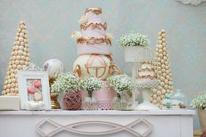 Elegant sweet table with big cake and macaroon on dinner