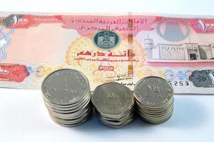 Cerca de varios billetes y monedas de Emiratos Árabes Unidos