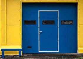 Texture of modern yellow garage wall with closed blue gate photo