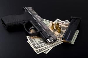 pistola con bala en billetes de dólar estadounidense